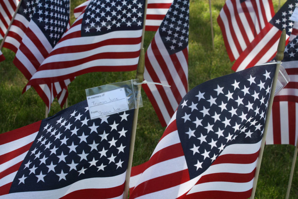 """flags on lawn, one showing tag saying """"in memory of Truman June from Sharon June"""