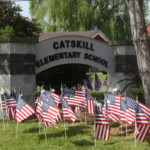 flags on lawn in front of Catskill Elementary School sign