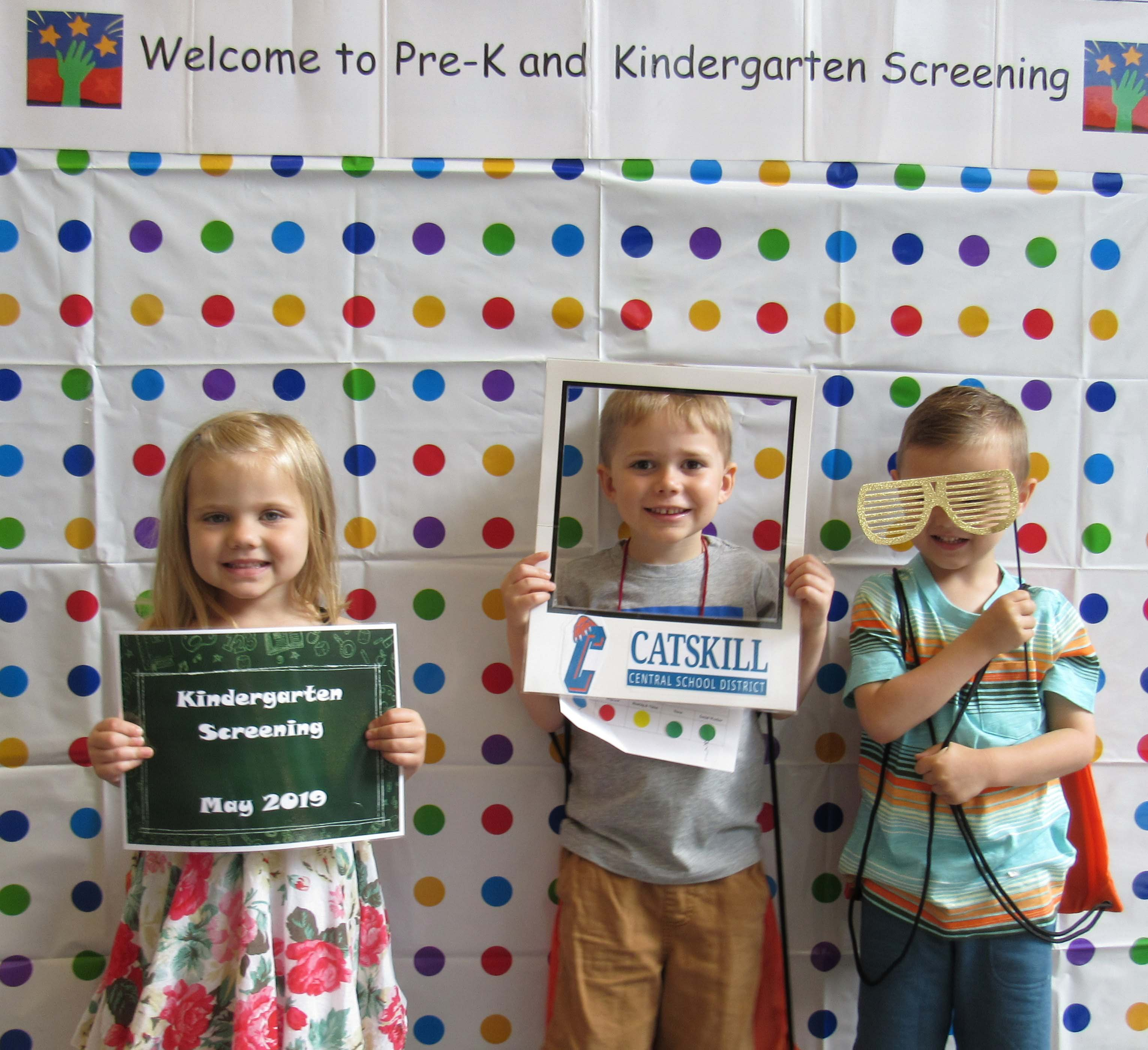 one girl and two boys pose with sign, frame, and silly glasses