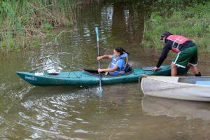 teacher launching girl in kayak