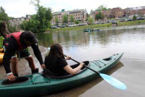 teacher prepares to lauch girl sitting in kayak