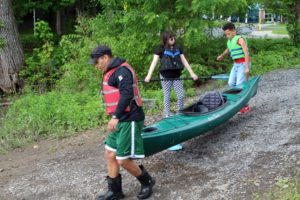 teacher and two students carry kayak to water