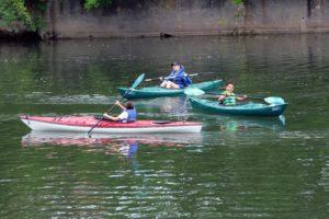 students nd teacher paddling on creek