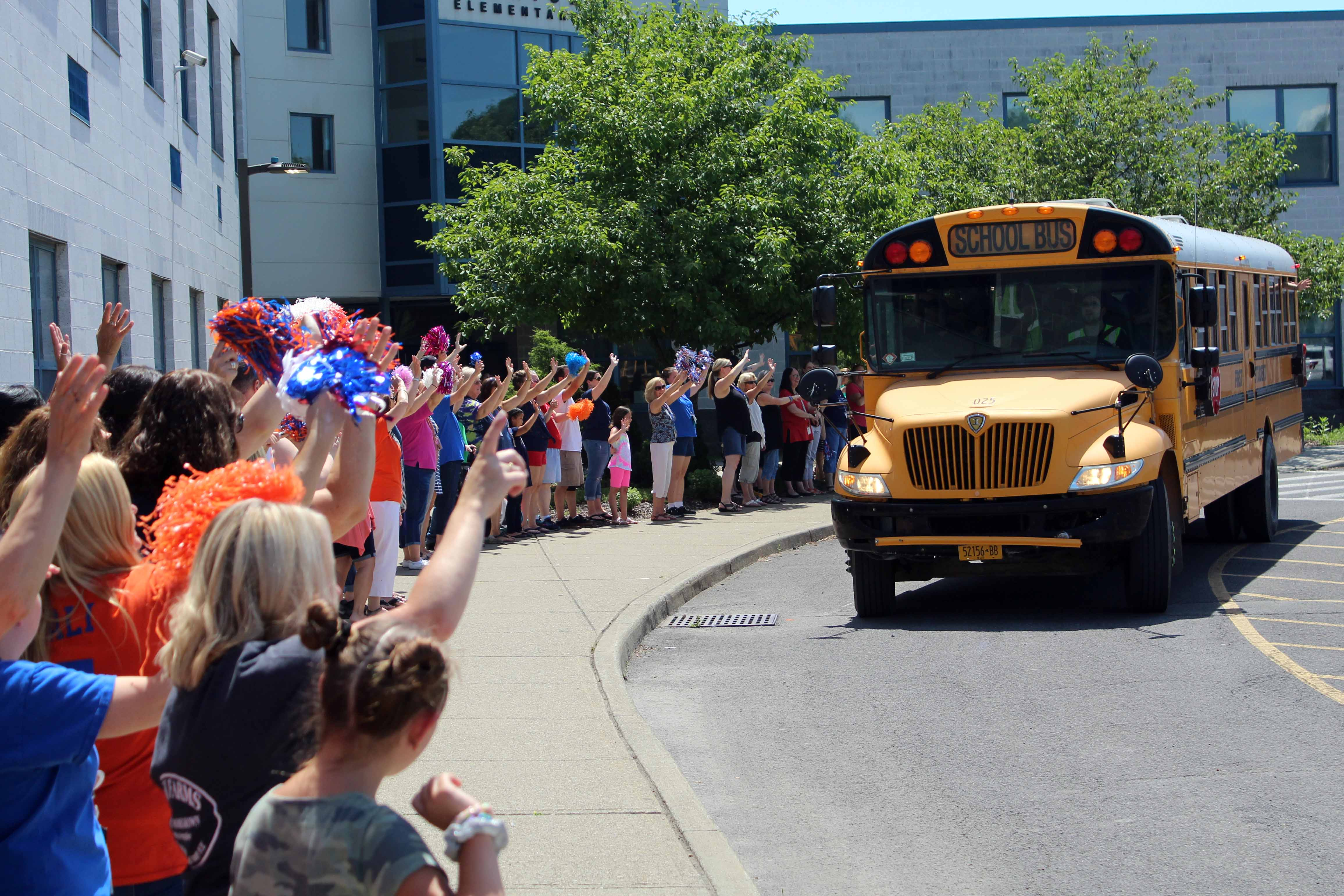 staff wave to bus as it leaves the parking lot