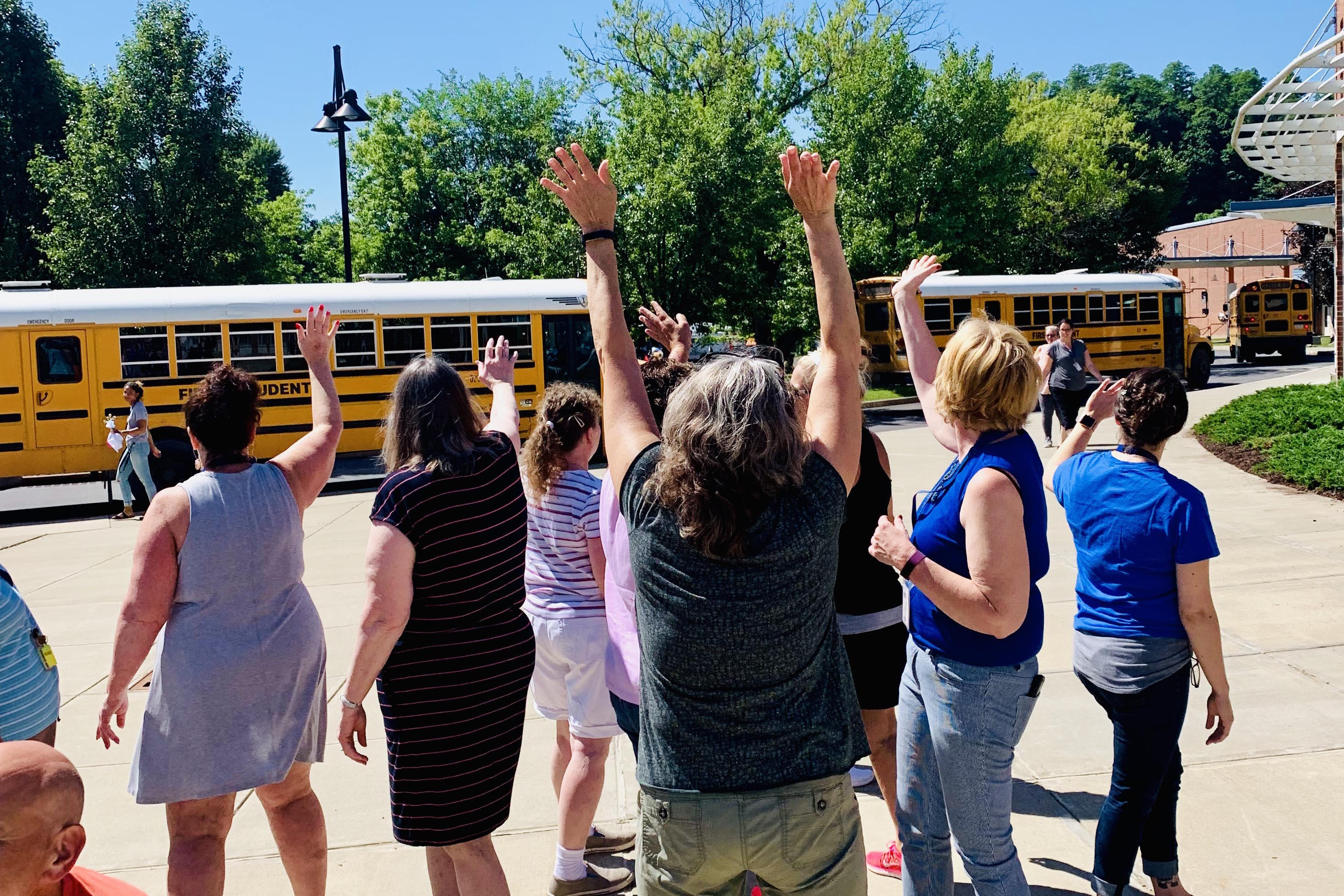 staff wave to buses leaving the parking lot