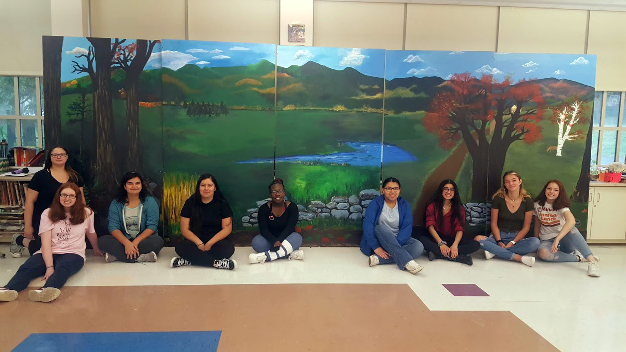 students pose with completed mural showing Catskill Mountains landscape