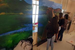 three girls painting mural