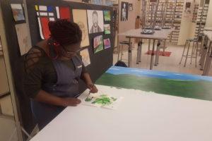 girl painting beginnings of mural