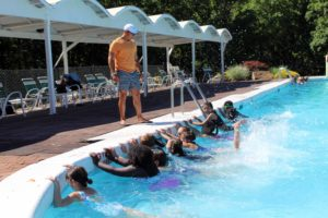 students practice kicking while holding onto pool side