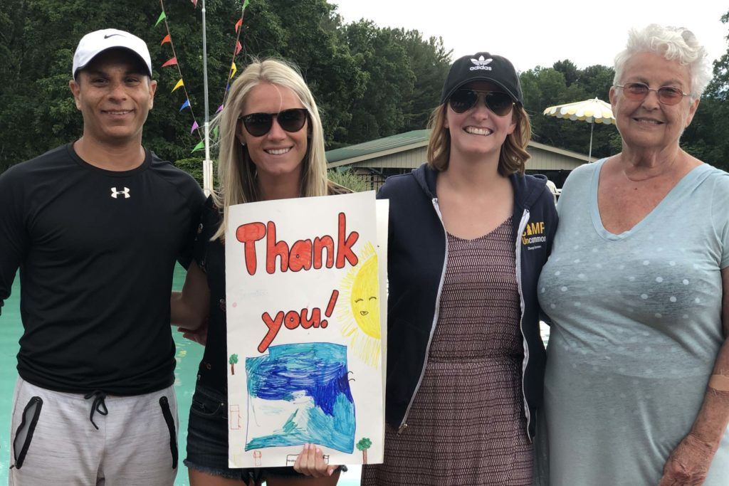 """PE staff pose with resort owner and poster that says """"thank you"""""""