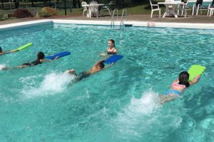 students swimming with kickboards