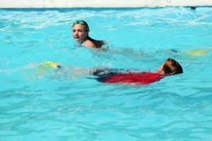 girl and boy pass one another swimming