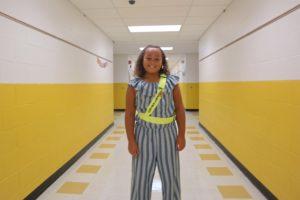 girl where safety patrol belt standing in hallway