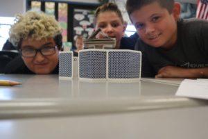 three boys building card house