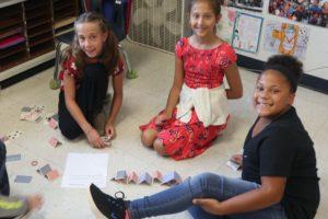 three girls building card house on floor