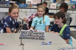 three girls building card house on table