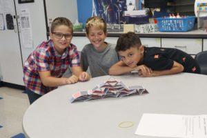 three boys building card house on table