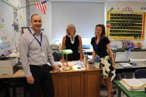 three teachers stansing around desk