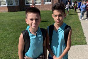 two boys wearing matching blue shirts