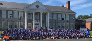 Middle School Student Body all weaing blue shirts on the school steps