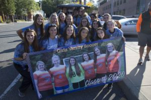 girls varsity soccer team holding team banner with photos of senior players