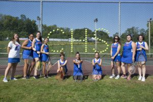 tennis team with CHS written in cups on tennis court fence