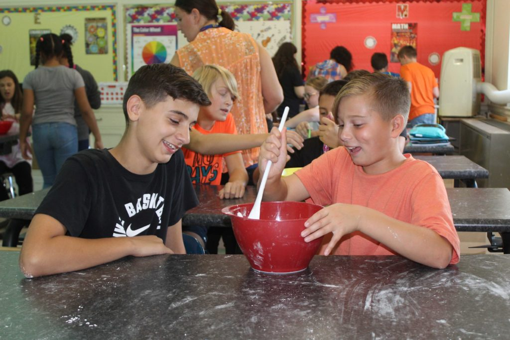 two boys using spoon and mixing bowl