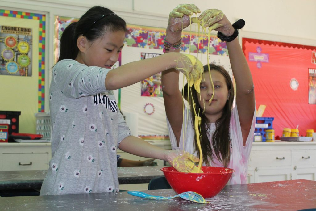 two girls dangle oobleck from thier fingers