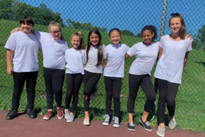 seven girls all wearing white t-shirts and black pants