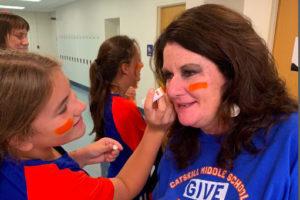 student applying makeup to staff member