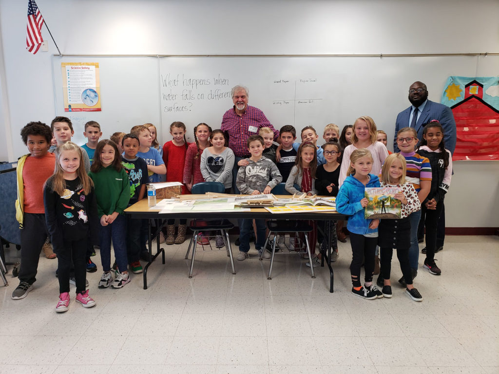 Hudson Talbott poses with third grade students and Dr. Cook at table with his books