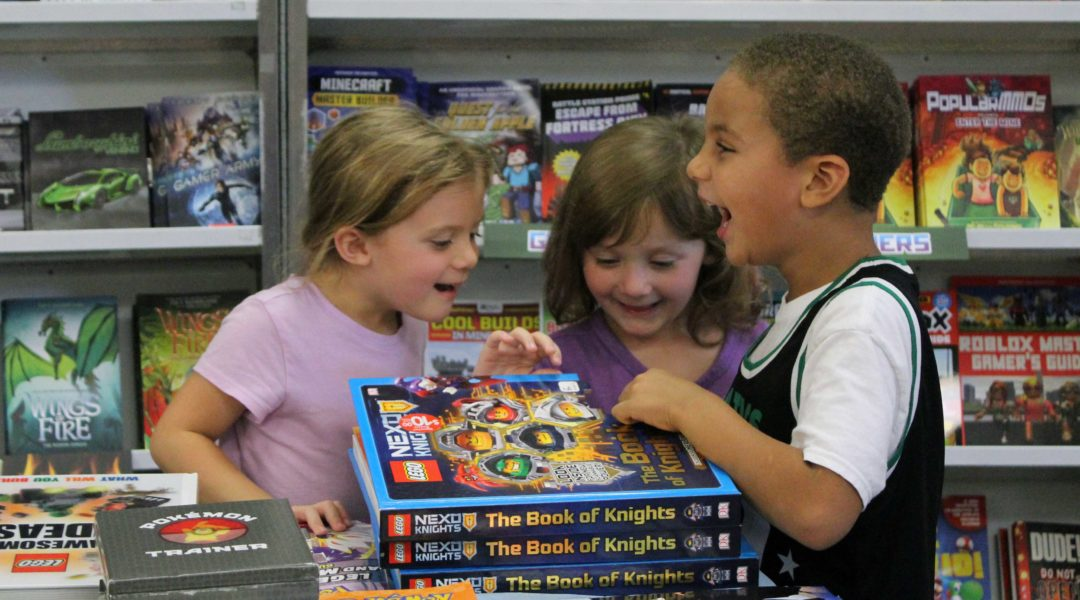 students loking at books and laughing