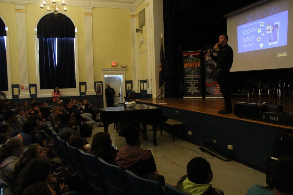Ryan Dutcher talks to audience of students in auditorium