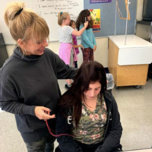 woman dressing girl's hair
