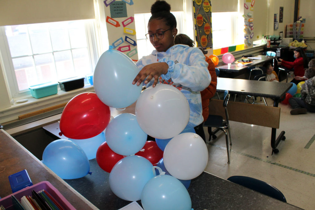 girl building balloon tower