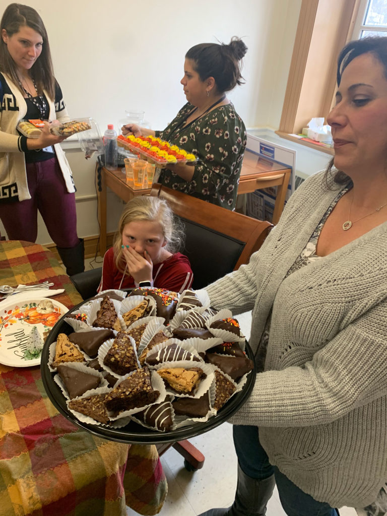teachers hold up trays of desserts