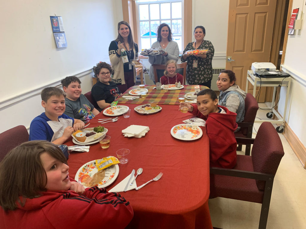 students eating turkey dinner at table while teachers hold up trays of desserts