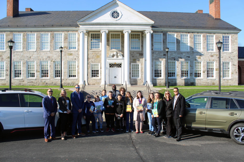 students, teachers, administratos, and Lacy family members pose with books and cars in front of Catskill Middle School