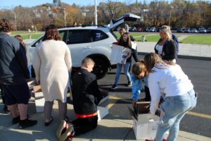 Students unload books from car