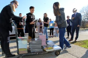 students stack books on cart