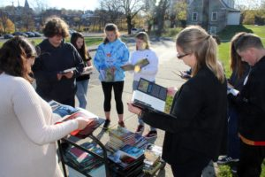 students and teacher flipping through books