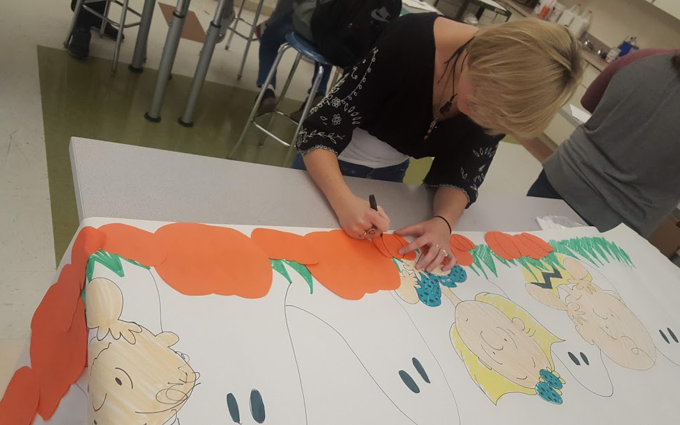 girl working on mural showing pupkins