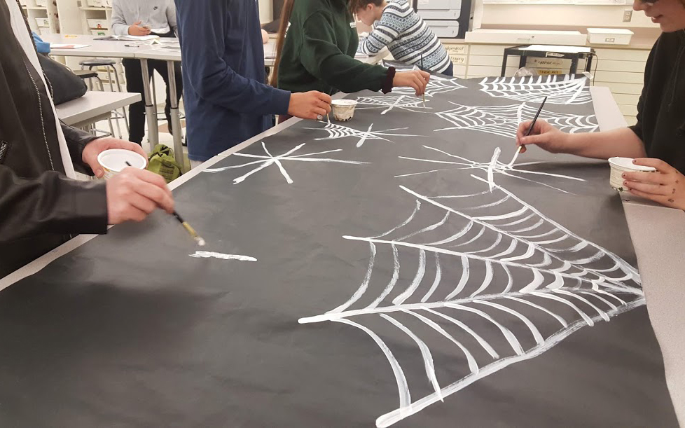 students working on mural showing of spiderwebs