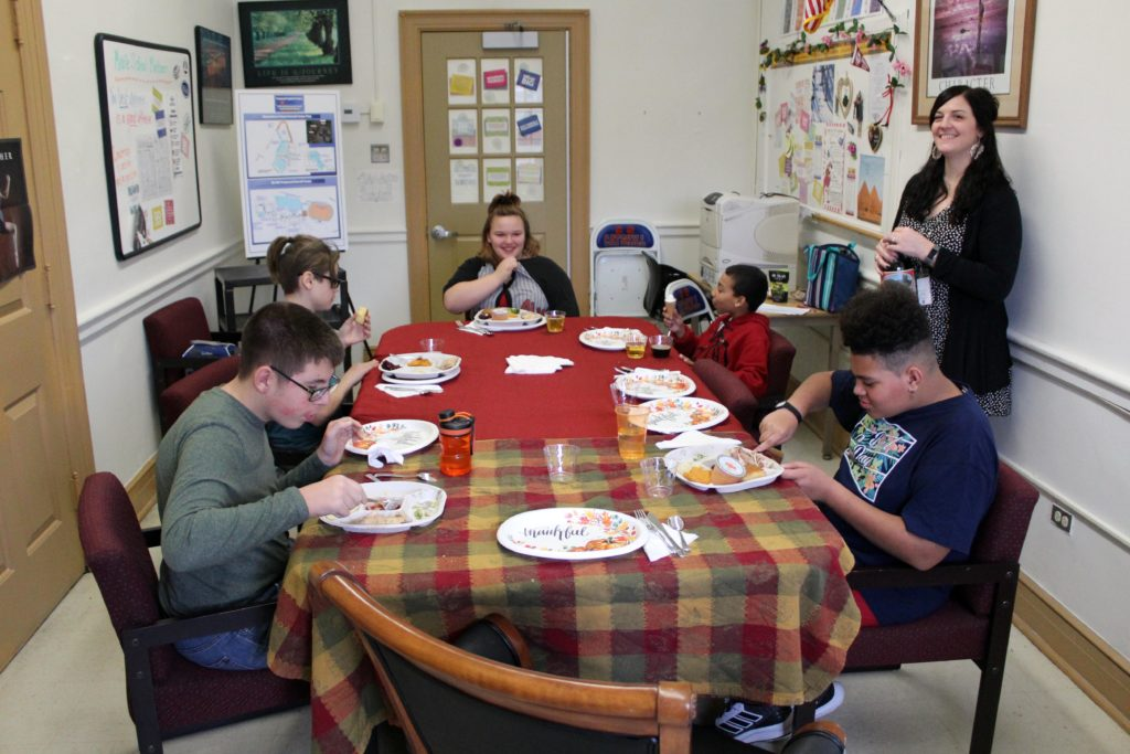 students eating meal at table while being served by teachers.