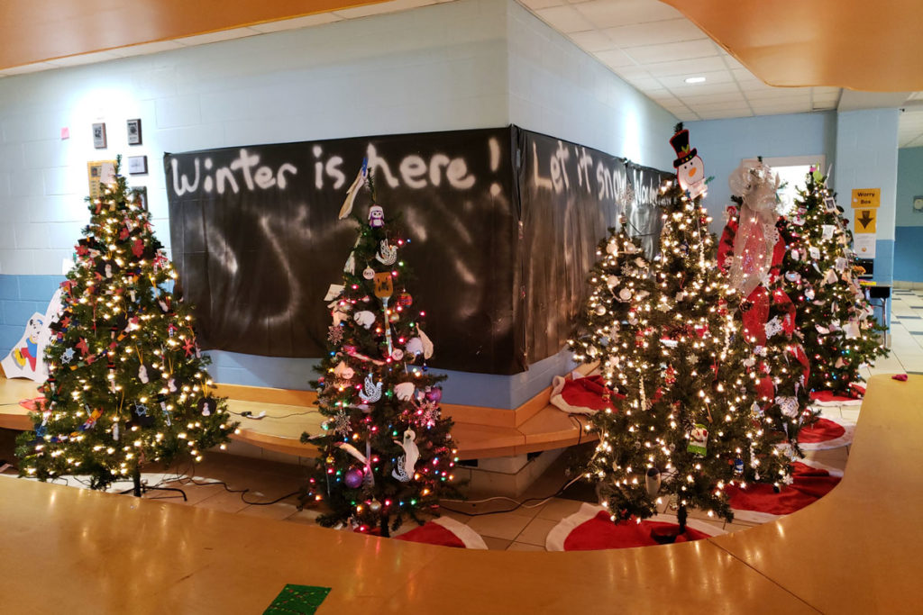 trees in lobby with banner that says winter is here