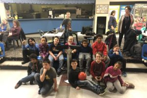 group photo of students and teachers sitting at bowling lane