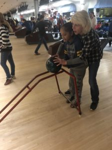 woman helping girl bowl with training ramp