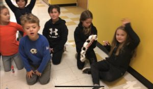 students kneeling on floor near and holding paper chain
