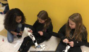 three girls making paper chains on floor