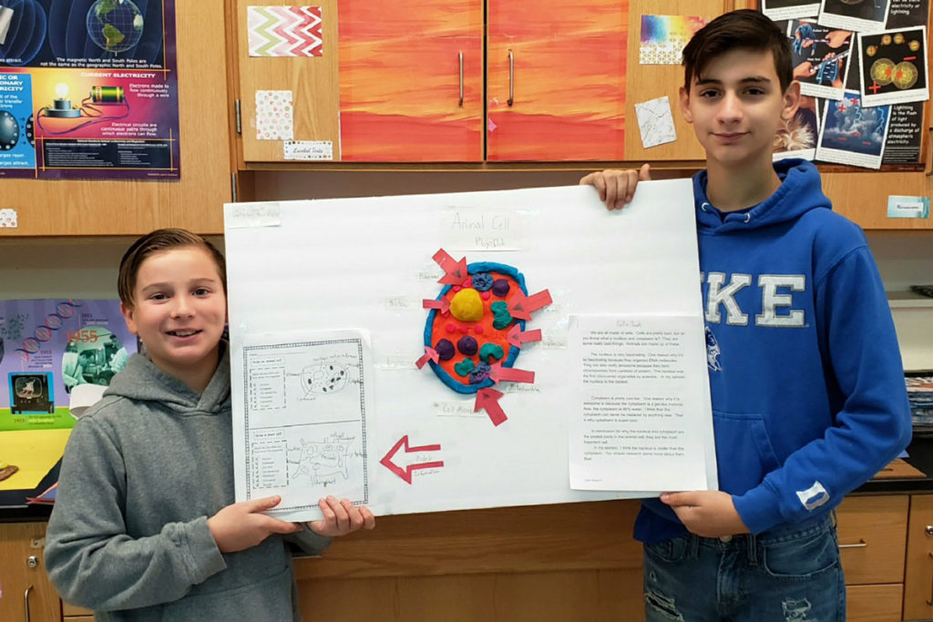 two boys hold up poster with 3D cell on it